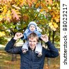 young father with his son spending time outdoor in the autumn park - stock photo