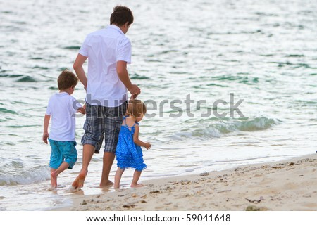 Young father with his two kids walking along tropical white sand beach at evening time - stock photo