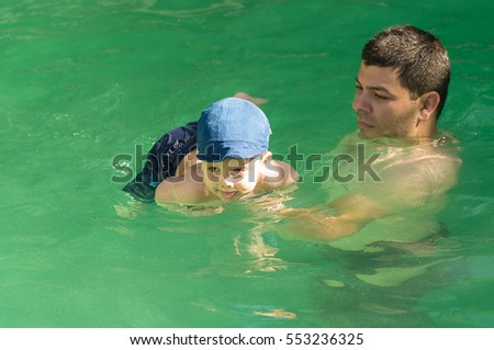 Young father with little son in pool