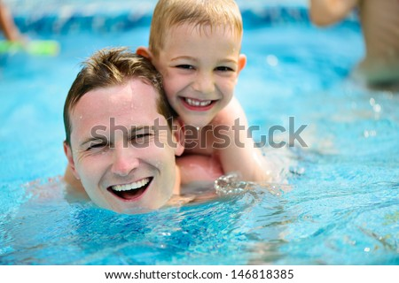 Young father with little son swimming in pool - stock photo