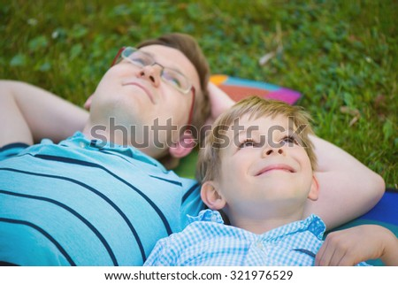 Young father with little sun dreaming at summer park - stock photo