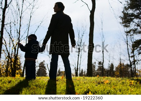 Young father with son enjoying beautiful autumn day - stock photo
