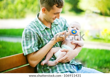 Young father with son outdoors in park, soft focus (focus on eyes of father) - stock photo