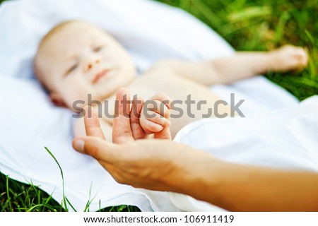 Young father with son outdoors in park, soft focus (focus on hands) - stock photo