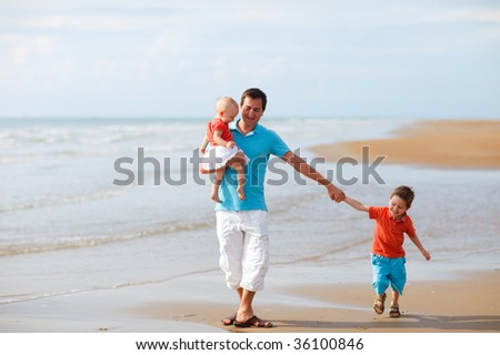 Young father with two kids at the beach