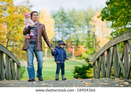 Young father with two kids enjoying beautiful autumn day - stock photo