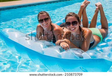 Young female adults smiling and relaxing floating in pool on raft.
