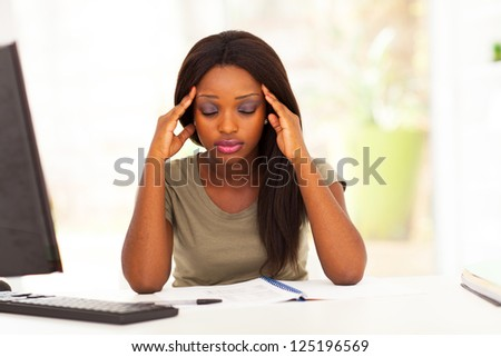 young female african american college student having headache - stock photo