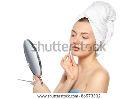 Young female after bath cleaning her skin with cotton pad, looking in mirror, isolated on white background - stock photo