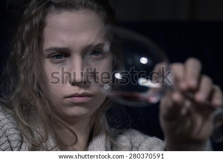 Young female alcoholic holding empty glass of wine - stock photo