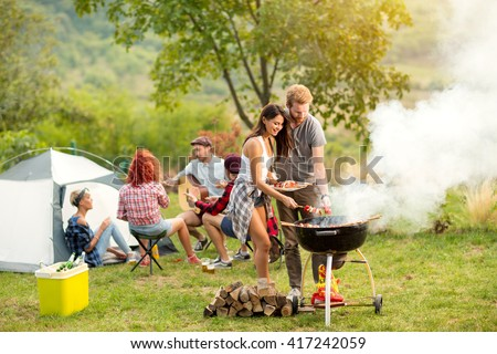 Young female and male couple baking barbecue in nature - stock photo