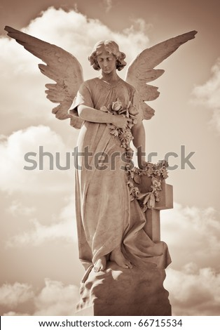 Young female angel in sepia tones standing against a dramatic sky - stock photo