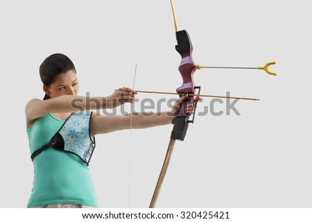 Young female archer practicing archery against gray background - stock photo