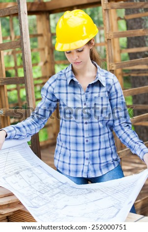 Young female architect analyzing blueprint in incomplete wooden cabin at construction site