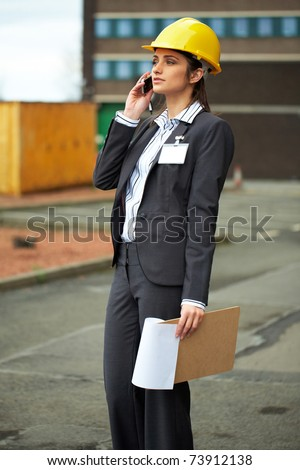 young female architect in yellow hard hat talks over mobile phone, construction site - stock photo