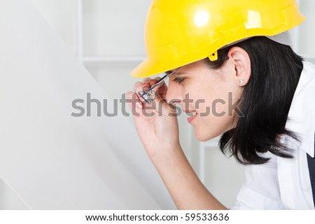 young female architect looking at blue print - stock photo