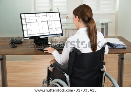 Young Female Architect On Wheelchair Looking At Blueprint On Computer In Office - stock photo