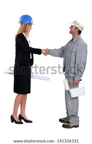 young female architect shaking hands with painter - stock photo