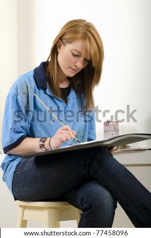 Young female artist at work in studio - stock photo