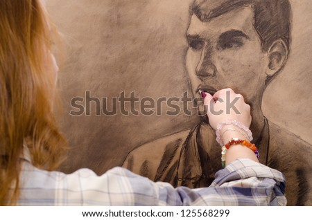 Young female artist drawing man portrait in her art studio. - stock photo