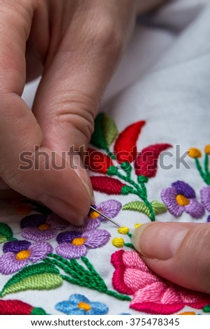 Young female artist performing her traditional embroidery day and night. - stock photo