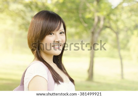 Young female Asian teen student standing on campus lawn, with backpack and smiling. - stock photo