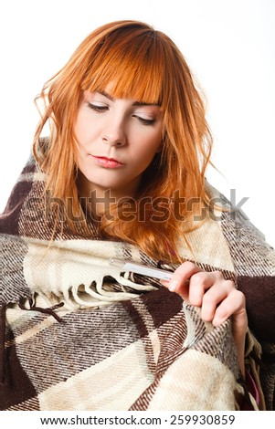 Young female at home having flu, feeling bad, taking her temperature in bed - stock photo