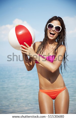 young female at the beach playing ball - stock photo