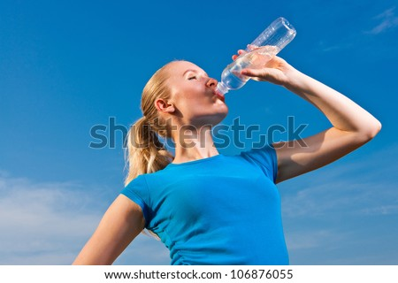 young female athlete drinking water to refresh during a hot weather running/training, blue sky background - stock photo