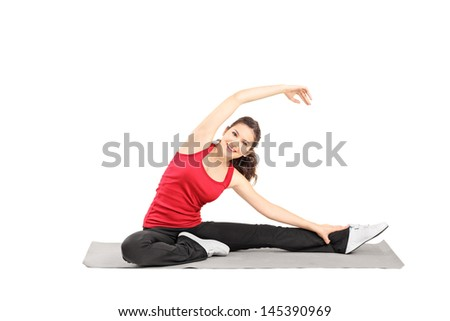 Young female athlete exercising on a mat isolated against white background - stock photo