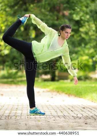 Young female athlete is doing stretching and balance exercise in nature. She is standing on one leg and holding other, stretching her thighs. - stock photo