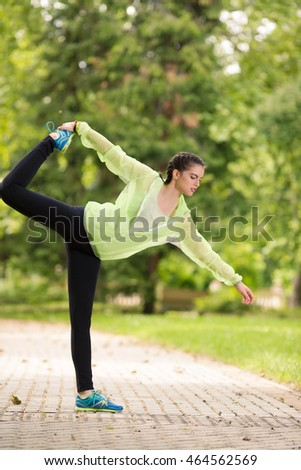 Young female athlete is doing stretching and balance exercise in nature. She is standing on one leg and holding other, stretching her thighs.