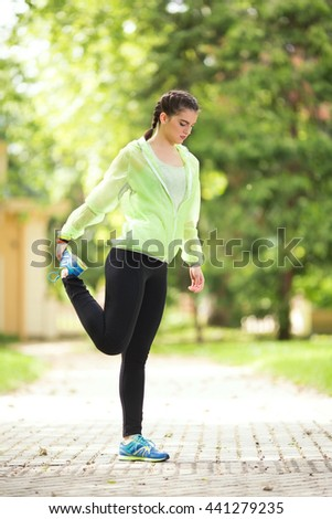 Young female athlete is doing stretching exercise in nature. She is standing on one leg and holding other, stretching her thigh. - stock photo
