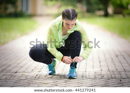 Young female athlete is tying shoelace on her sports shoe before exercise in nature. - stock photo