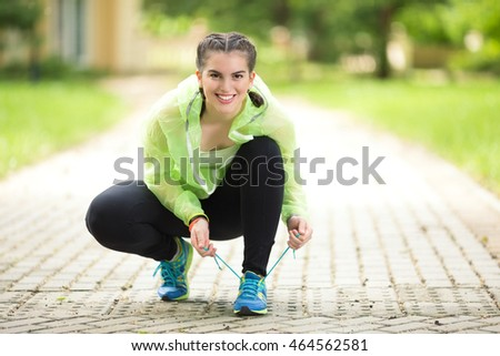 Young female athlete is tying shoelace on her sports shoe before exercise in nature. She is smiling and looking at camera.