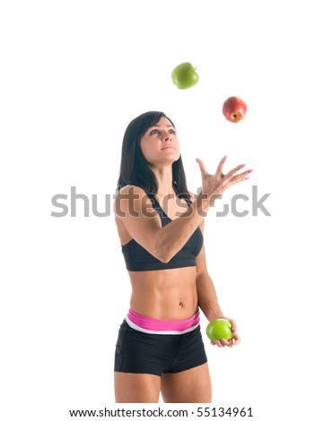 Young female athlete juggling red and green apple