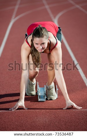Young female athlete on a running track, ready to go from starting blocks - stock photo