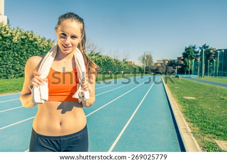 Young female athlete on a running track with a towel after hard training - Beautiful caucasian woman relaxing after running in a sport centre - Concepts about sport,wellness and recreation