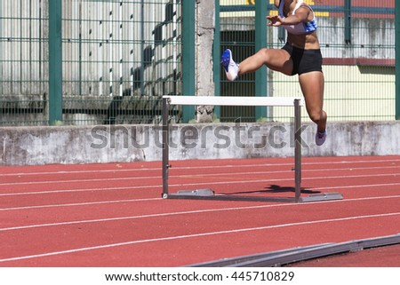 young female athlete running the obstacle course - stock photo