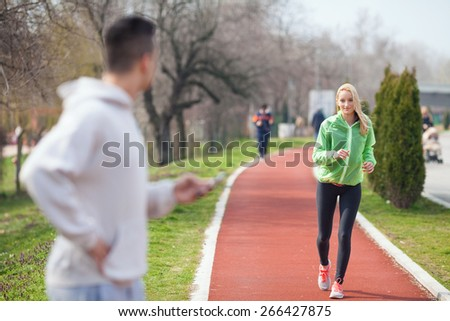 Young female athlete running.Unrecognizable sport instructor looking at his student and measuring her results - stock photo