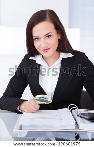 Young female auditor scrutinizing financial documents at desk in office