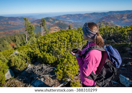 Young female backpacker resting on mountain peak with cup of tea/coffee, enjoying view of valley below. Colorful autumn time. - stock photo