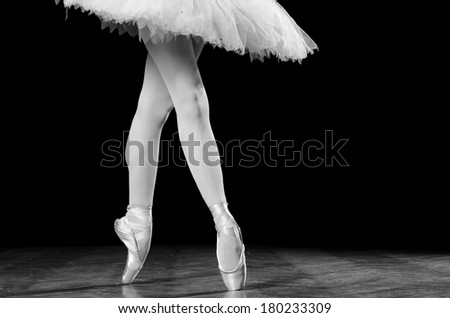 Young female ballerina standing on toes, close up shot of legs - stock photo