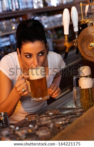 Young female bartender tasting draft beer in bar