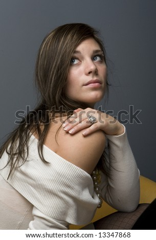 Young female beauty gazing up with hand on shoulder, side view. - stock photo