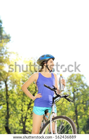Young female biker posing on a mountain bike outdoors on a sunny day - stock photo