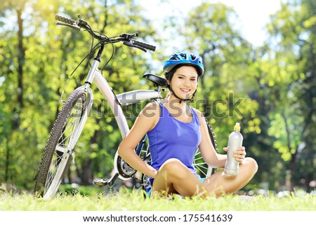 Young female biker sitting on a green grass next to a bike and drinking water - stock photo