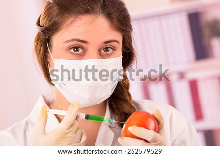 young female biologist injecting a syringe in a tomato concept of genetically modified food - stock photo