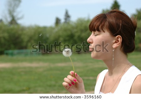 Young female blowing dandelion in a sunny day - stock photo