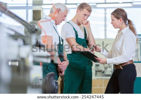 Young female boss checking her employees work - stock photo